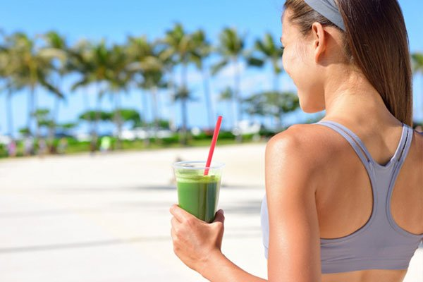 Photo of healthy young woman drinking green smoothie